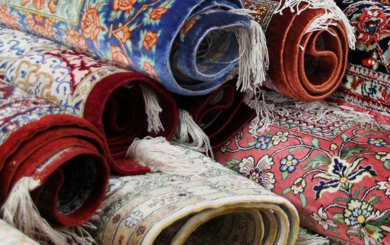 Stack of rolled hand woven rugs