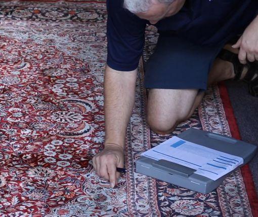 Kurt Gilbertson pre-inspecting a rug